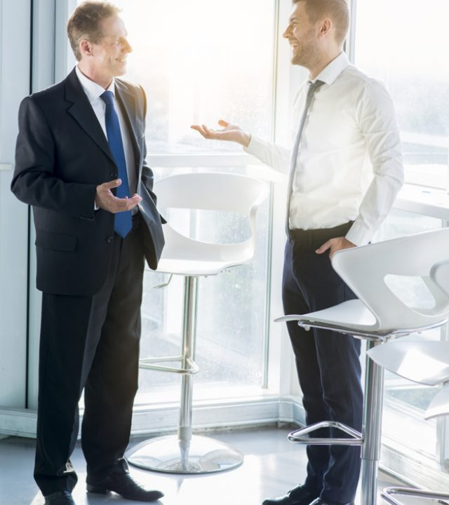 two-happy-businessmen-standing-near-window-talking-with-each-other-office_23-2147899766